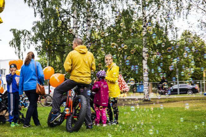 Ihmisiä saippuakuplien seassa puistossa