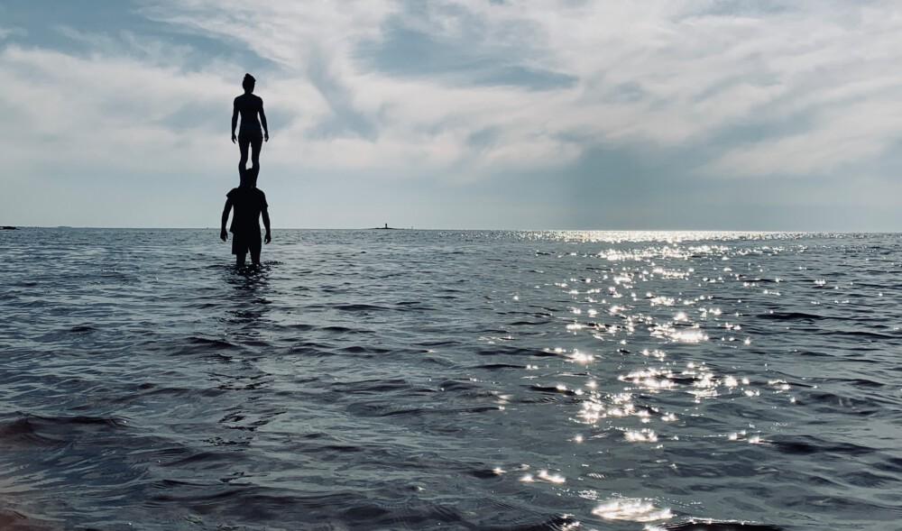 nainen seisoo miehen olkapäillä meressä